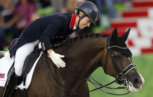 British rider Charlotte Dujardin celebrates with her horse Valegro during Team Competition Dressage at the World Equestrian Games at the d'Ornano stadium in Caen, France, in 2014. Britain team won ...