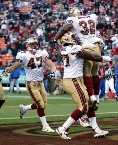 As San Francisco 49ers tight end Billy Bajema (47) runs to join in, 49ers tackle Kwame Harris (77) lifts 49ers running back Kevin Barlow (32) into the air after Barlow ran for a 10-yard touchdown  ...