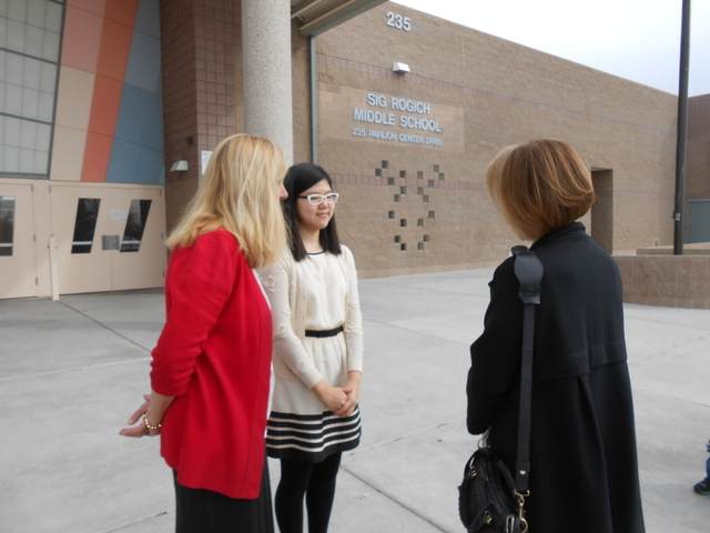 Esther Hong and her history teacher, Lori Figgins, left, talk with Linda Alterwitz, director of community projects for Walker Furniture, right, March 11, 2015, outside Rogich Middle School. Alterw ...