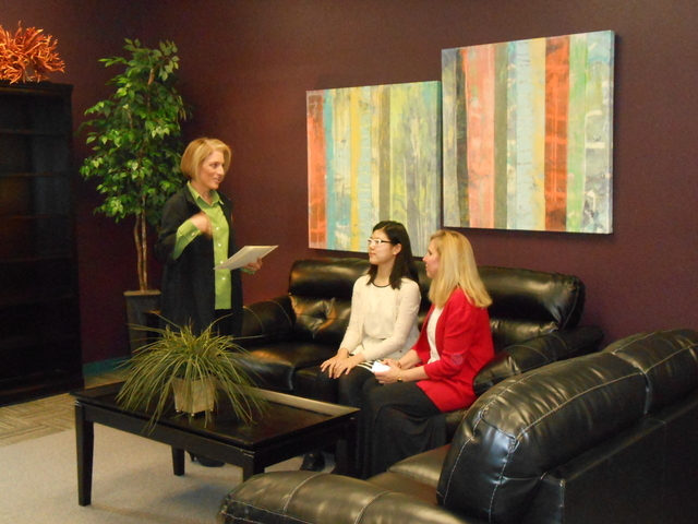 Esther Hong and her history teacher, Lori Figgins, seated talk with Linda Alterwitz, director of community projects for Walker Furniture, standing, March 11, 2015, in the newly furnished teachers' ...