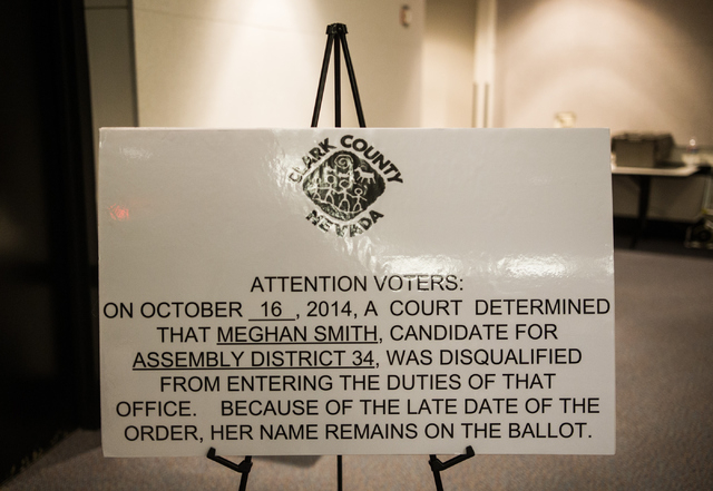 A sign stating that Assembly District 34 candidate Meghan Smith has been disqualified is seen at the early voting polling site at Sahara West Library in Las Vegas on Wednesday, Oct. 22, 2014. (Cha ...