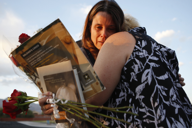 Jamie Diedrich, mother of Joshua Phillips who died in an U.S. Army airborne training accident, embraces friend Annjanette Ranney during a candle light vigil for her son at the Legacy High School f ...