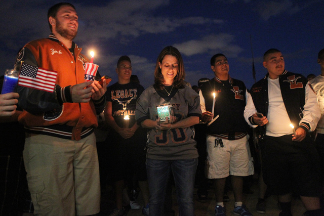 Jamie Diedrich, center, mother of Joshua Phillips, 19, who died in an U.S. Army airborne training accident, stands during a candle light vigil for her son at the Legacy High School football field  ...