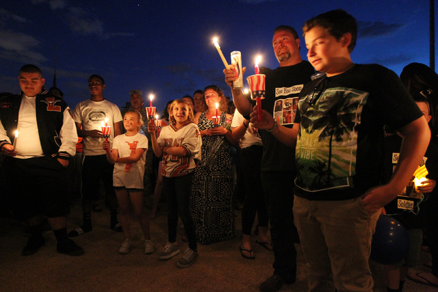 Troy Phillips, second from right, father of Joshua Phillips, 19, who died in an U.S. Army airborne training accident, stands during a candle light vigil for her son at the Legacy High School footb ...