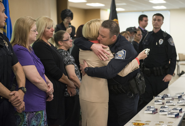 North Las Vegas Police Officer Kevin Karaer, center, embraces victim family member Pamela Walker as she presents Officer Karaer with an engraved handcuff as a sign of appreciation during the Ride  ...