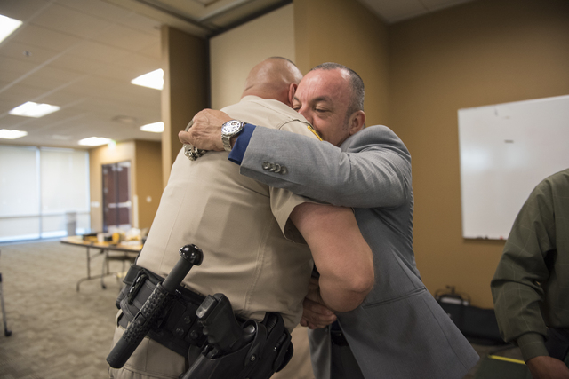 Las Vegas Metro Police Officer Dwaine McCuistion, left, embraces victim family member Arcadio Bolones, as he presents Officer McCuistion with an engraved handcuff as a sign of appreciation during  ...