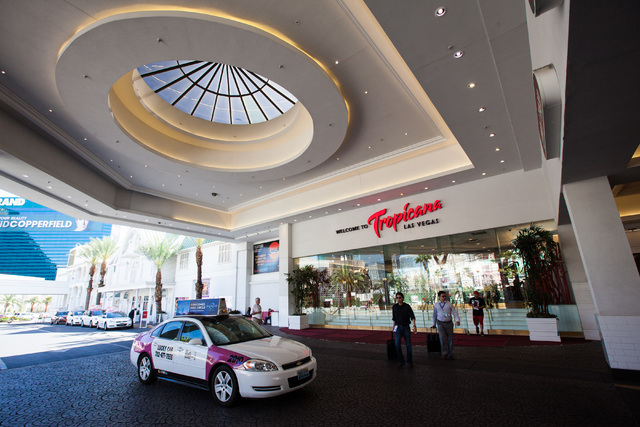 People pass by underneath the porte-cochre of the Tropicana hotel-casino in Las Vegas on Wednesday, April 29, 2015. Penn National Gaming announced an agreement to acquire the Tropicana for $360 mi ...