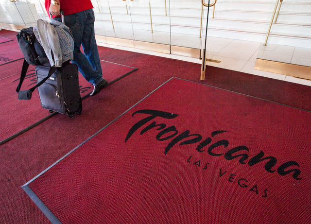 A man with luggage walks outside of the Tropicana hotel-casino in Las Vegas on Wednesday, April 29, 2015. Penn National Gaming announced an agreement to acquire the Tropicana for $360 million. (Ch ...