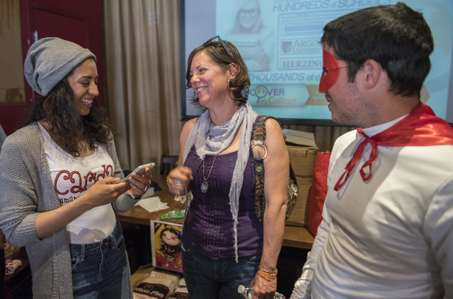 "President/CEO Merideth Spriggs of Caridad Humanizing the Homeless, left, speaks to Amy Sinclair, center, and Joe Troia aka ""Mighty Tighty"" the sock and underwear hero, during a sock and  ..."