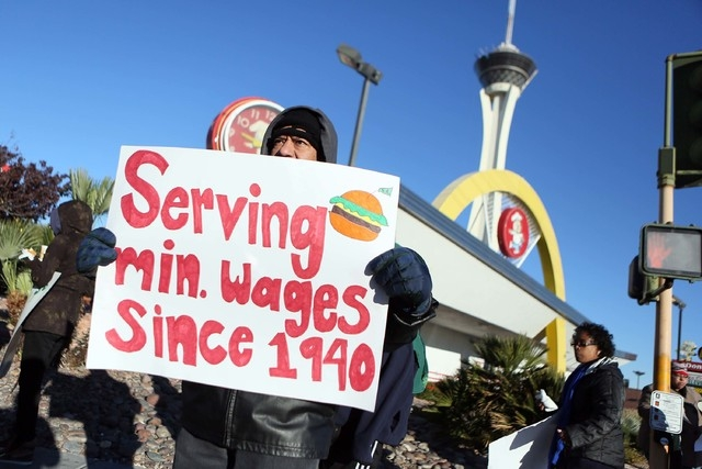 Cesar Torres holds a sign during a protest outside McDonald's on 2248 Paradise Road Thursday, Dec. 5, 2013, in Las Vegas. Community members and fast-food workers gathered as part of a natio ...