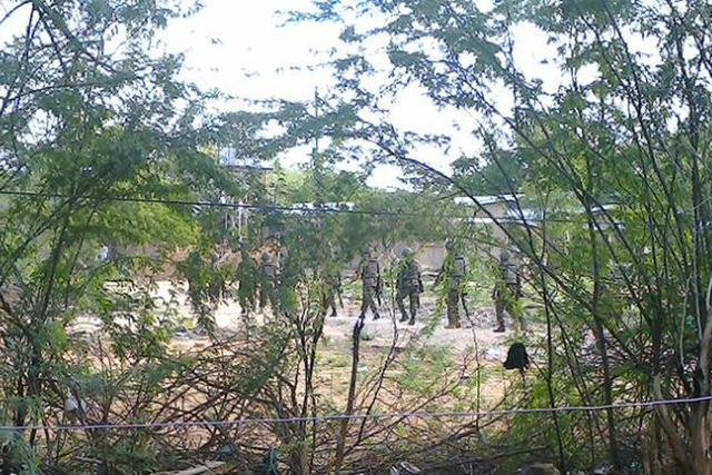 Kenya Defence Forces soldiers move behind a thicket in Garissa town in this photograph taken from a mobile phone April 2, 2015. Masked gunmen stormed the campus at Garissa University College in no ...