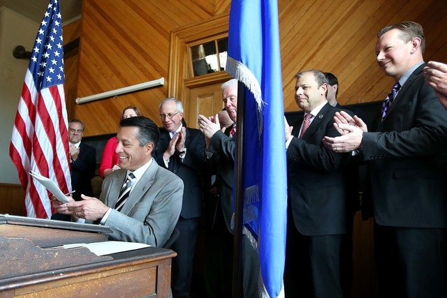 Nevada Gov. Brian Sandoval signs a bill on Monday, April 13, 2015, that gives tax breaks to businesses that donate to a scholarship program for disadvantaged students to attend private schools. Su ...