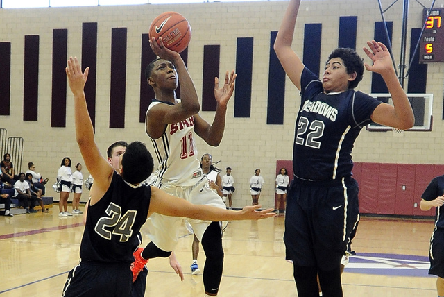 Agassi Prep guard Deishuan Booker (11) is fouled by The Meadows forward Michael Jin (24) while center Max Hisatake (22) defends during their prep basketball game  at Agassi Prep High School in Las ...