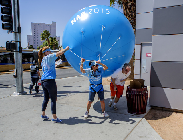 Cindy Dahlstedt,left, and Emily-Kate Niskey struggles to regain control of a balloon display on the corner of Paradise Road and Convention Center Drive on Tuesday, April 14, 2015. The National Wea ...