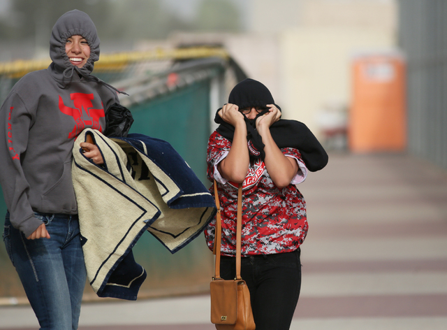 Arbor View High School students Vanessa Lourenco, left, and Amaris Calderon run back to the bleachers in the wind after retrieving additional items of clothing when the weather turned during an Ar ...