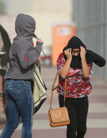 Arbor View High School students Vanessa Lourenco, left, and Amaris Calderon shield themselves from the wind as they run back to the bleachers after retrieving additional items of clothing when the ...