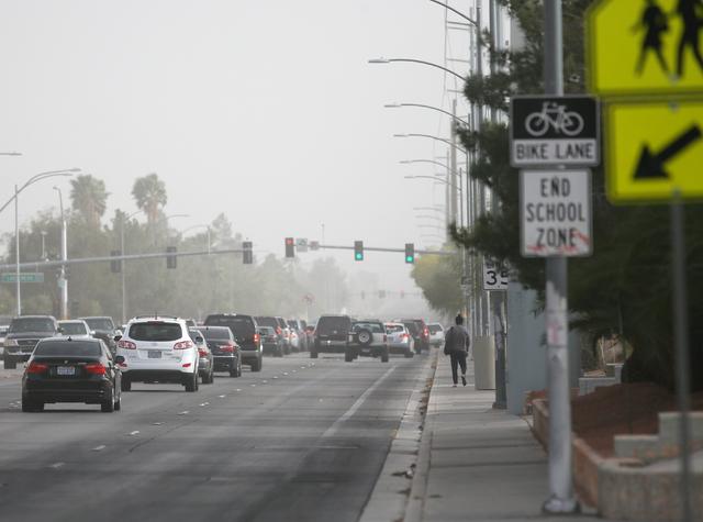 Cars make their way through dust and debris on a windy day along Tenaya Way near Cimarron-Memorial High School Tuesday, April 14, 2015, in Las Vegas. (Ronda Churchill/Las Vegas Review-Journal)
