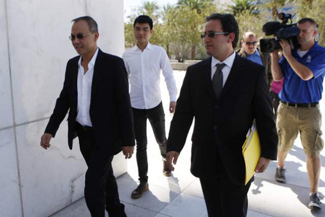 Paul Phua, left, and his son Darren, center, walk to Lloyd George U.S. Courthouse in Las Vegas with their attorney Richard Schonfeld for their arraignment Aug. 5, 2014. The two are charged in a mu ...