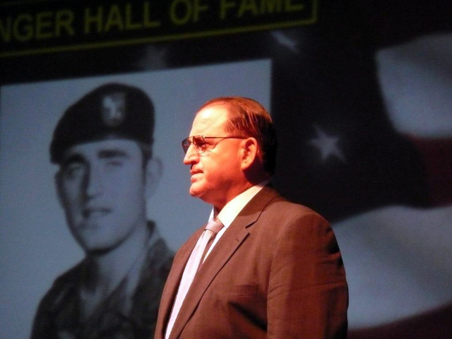 U.S. Army veteran Bill Anton of North Las Vegas stands as his service photo is projected on a screen during his Army Ranger Hall of Fame induction ceremony at Fort Benning, Ga., Aug. 5, 2009. (Pho ...