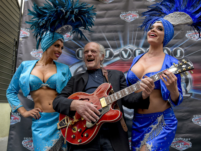 """Actor Christopher Lloyd, center, entertains showgirls with Marty McFly's guitar as he waits to go onstage at the Fremont Street Experience in Las Vegas with other """"Back To The Future"""" ca ..."""