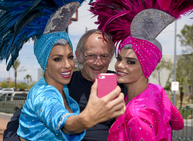 """Actor Christopher Lloyd, center, poses for a selfie with showgirls under the """"Welcome to Fabulous Las Vegas"""" sign as he and other cast members of the movie """"Back to the Future"""" ..."""