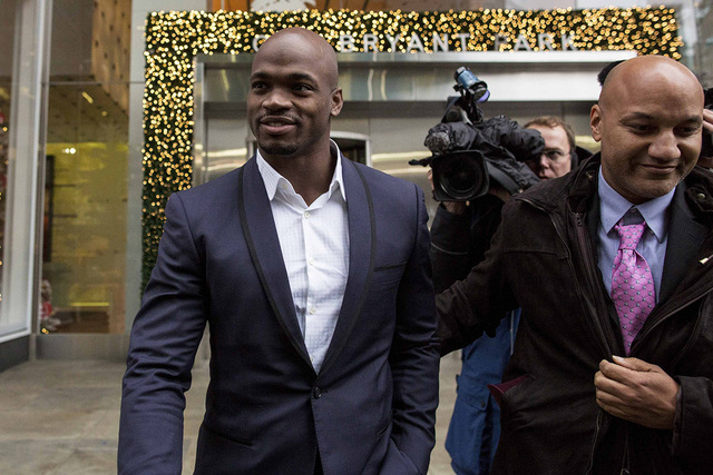 Suspended Minnesota Vikings running back Adrian Peterson (L) exits following his hearing against the NFL over his punishment for child abuse, in  New York December 2, 2014. Peterson was suspended  ...