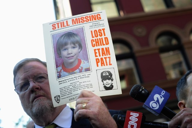 New York Police Department spokesman Paul Brown holds an original missing poster of Etan Patz during a news conference near a New York City apartment building, where police and FBI agents were sea ...