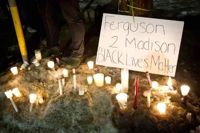 Candles are piled in the snow outside the home of Tony Robinson Jr. during a candlelight vigil on Williamson Street in Madison, Wisconsin, March 8, 2015.  (REUTERS/Ben Brewer)