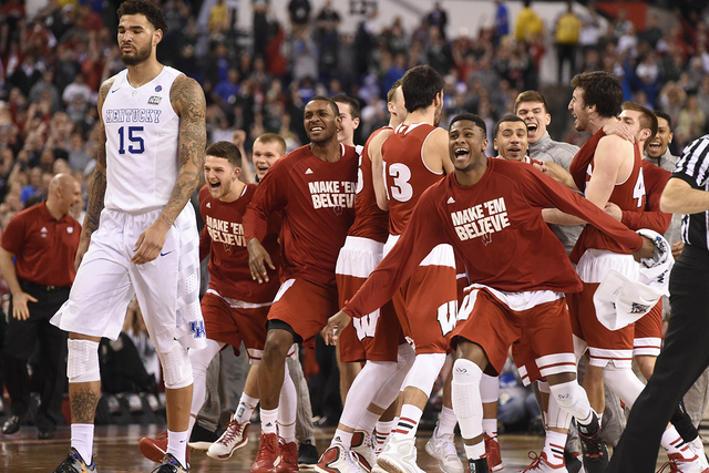 Apr 4, 2015; Indianapolis, IN, USA; Wisconsin Badgers celebrate as Kentucky Wildcats forward Willie Cauley-Stein (15) walks off the court as they upset Kentucky 71-64 in the 2015 NCAA Men's Divisi ...