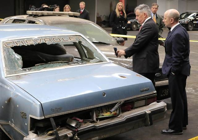 Cuyahoga County prosecutor Tim McGinty (L) takes a photo with his cell phone at a mock up of the crime scene during the manslaughter trial for a police officer in Cleveland, Ohio April 10, 2015. M ...