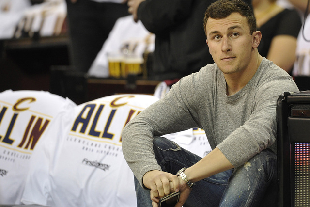 Apr 19, 2015; Cleveland, OH, USA; Cleveland Browns quarterback Johnny Manziel sits in the front row prior to game one of the first round of the NBA Playoffs at Quicken Loans Arena. (David Richard/ ...