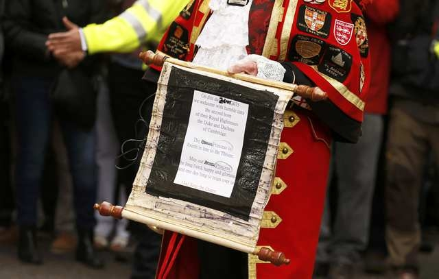 A ceremonial town crier holds a scroll after announcing the birth of a baby girl to royal fans and members of the media outside the entrance to the Lindo wing of St Mary's Hospital in London, Brit ...