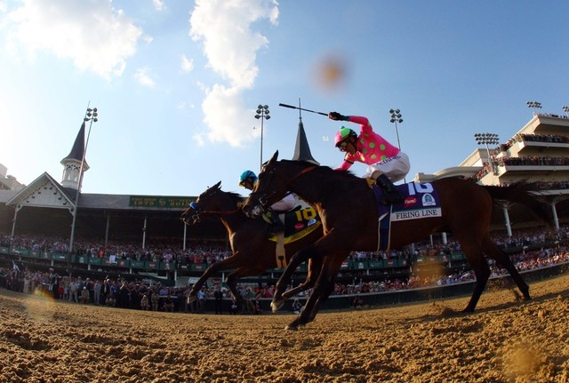 Victor Espinoza aboard American Pharoah passes Gary L. Stevens aboard Firing Line during the 141st Kentucky Derby at Churchill Downs, May 2, 2015. (Brian Spurlock-USA TODAY Sports)