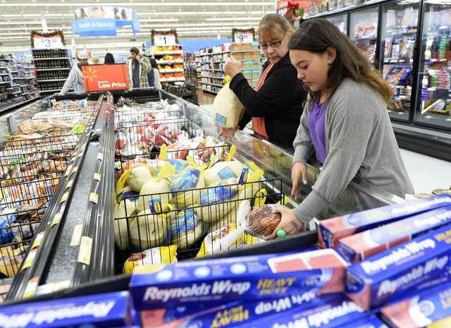 Tina Corpus and her daughter Christina shop for a turkey at a Walmart store in Los Angeles, California, United States, in this file photo taken November 26, 2013. The outbreak of fatal bird flu cu ...