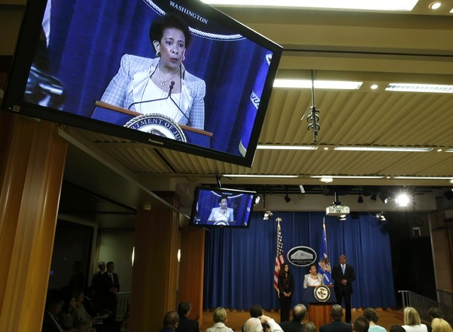 U.S. Attorney General Loretta Lynch is pictured on a television monitor as she addresses a news conference, where she announced a federal civil rights investigation into the legality of the Baltim ...