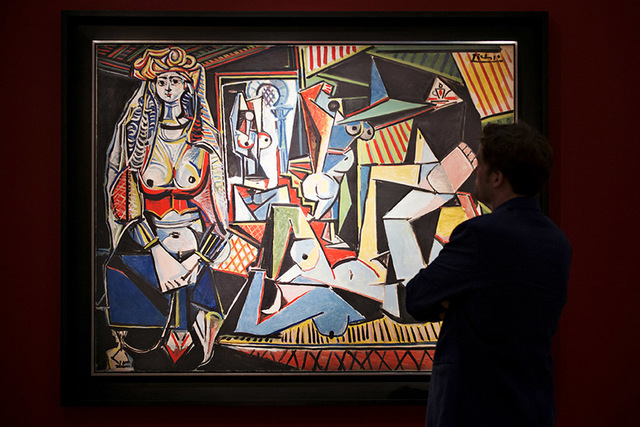 "A man pauses to look at Pablo Picasso's ""Les femmes d'Alger (Version 'O')"" (Women of Algiers). The 60-year-old painting fetched $179.4 million, including fees at Christie's on Monday. (REUTERS/D ..."