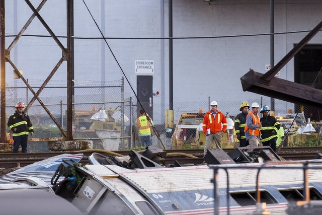 Emergency workers survey the remains of a derailed Amtrak train in Philadelphia, Pennsylvania May 13, 2015. An Amtrak passenger train with more than 200 passengers on board derailed in north Phila ...