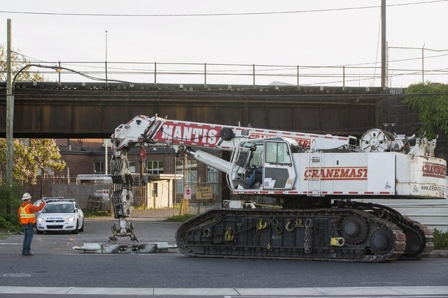 A worker gestures as a large crane arrives to help with the aftermath of a derailed Amtrak train in Philadelphia, Pennsylvania, May 13, 2015. (Reuters/Lucas Jackson)
