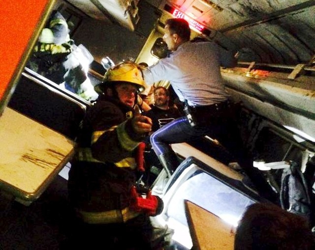 A rescuer searches for injured people inside the derailed Amtrak train in Philadelphia May 12, 2015 in a photo provided by former Pennsylvania Congressman Patrick Murphy, who was a passenger on th ...