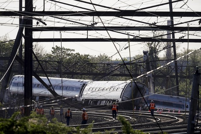 Officials survey the site of a derailed Amtrak train in Philadelphia, Pennsylvania, May 13, 2015. Rescue workers searched through the debris on Wednesday for more victims of an Amtrak passenger tr ...