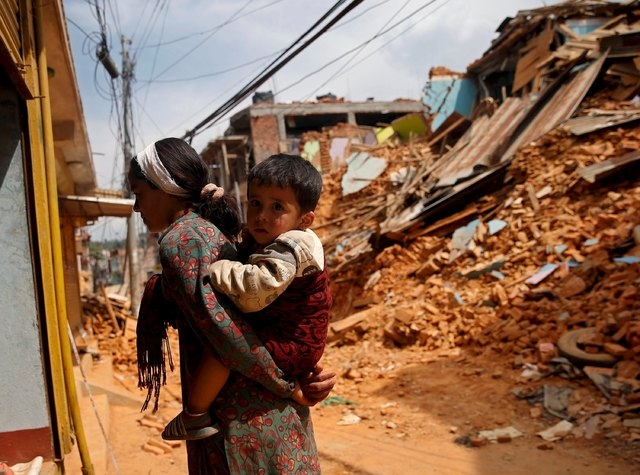 A woman carries her boy as she stands on a road which was damaged by earthquake, in Sindhupalchowk district, Nepal, May 13, 2015. REUTERS/Ahmad Masood