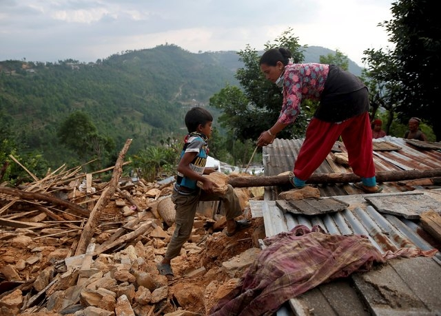 A boy helps her mother rebuild their house in Sindhupalchowk district, Nepal, May 13, 2015. The Himalayan nation is still reeling from a devastating earthquake measuring 7.8 last month that killed ...