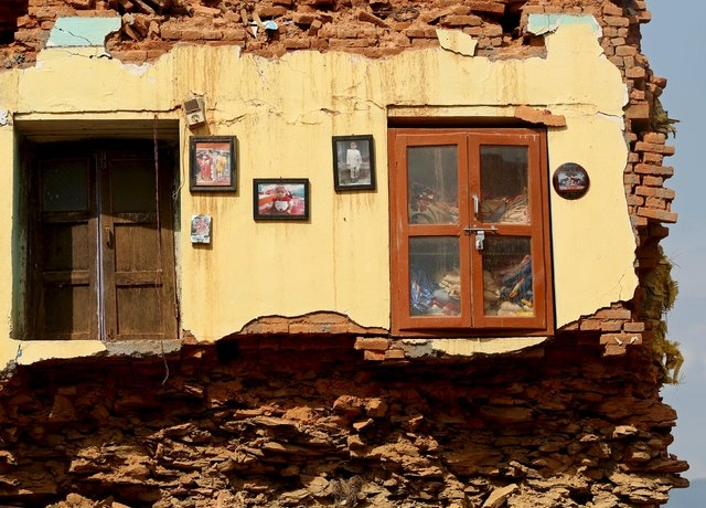 Framed pictures are seen hanging from the wall of a house damaged by earthquakes in Sindhupalchowk district, Nepal, May 13, 2015. (Reuters/Ahmad Masood)