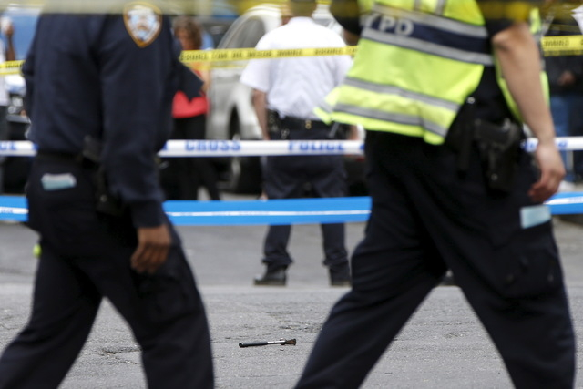 A hammer lies on the ground at a crime scene as members of the NYPD police stand by at the intersection of 37th street and 8th avenue in midtown Manhattan in New York, May 13, 2015.  (REUTERS/Shan ...