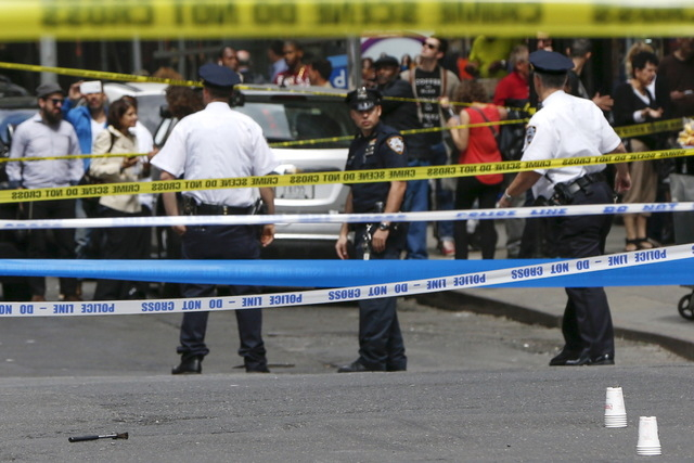Members of the NYPD police stand near the crime scene as a hammer (pictured left on the ground) lies on the ground, at the intersection of 37th street and 8th avenue in midtown Manhattan in New Yo ...