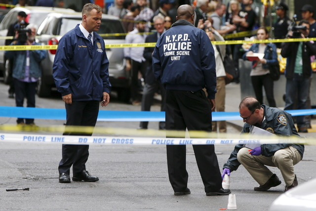 Members of the NYPD police investigate the crime scene as a hammer (pictured left on the ground) lies on the ground, at the intersection of 37th street and 8th avenue in midtown Manhattan in New Y ...