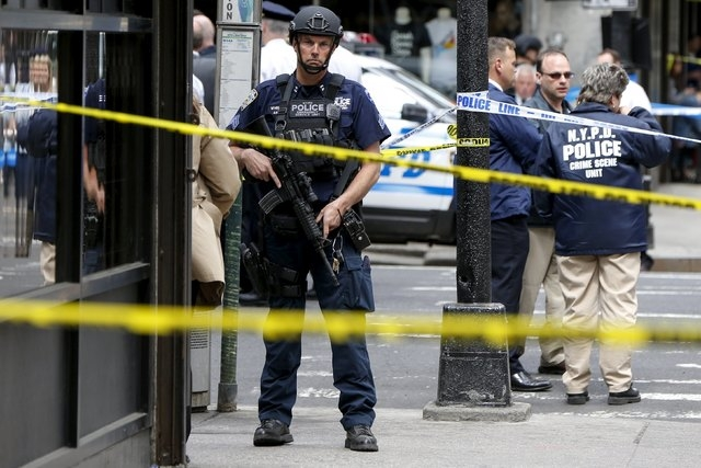 Members of the NYPD police stand near the crime scene at the intersection of 37th street and 8th avenue in midtown Manhattan in New York, May 13, 2015. (REUTERS/Shannon Stapleton)