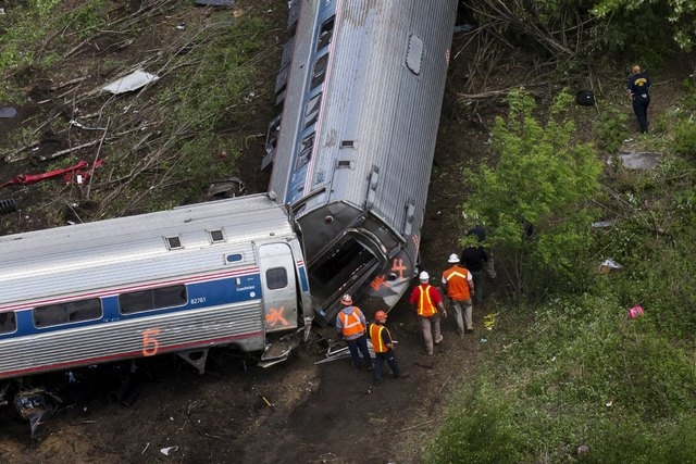 Emergency workers and Amtrak personnel inspect a derailed Amtrak train in Philadelphia, May 13, 2015.  The commuter rail route where an Amtrak train left the track on Tuesday was not governed by a ...