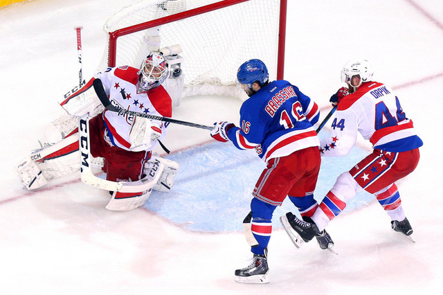 May 13, 2015; New York, NY, USA; Washington Capitals goalie Braden Holtby (70) makes a save in front of New York Rangers center Derick Brassard (16) and Washington Capitals defenseman Brooks Orpik ...