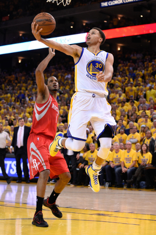 May 19, 2015; Oakland, CA, USA; Golden State Warriors guard Stephen Curry (30) shoots a layup against Houston Rockets forward Trevor Ariza (1) during the fourth quarter in game one of the Western  ...